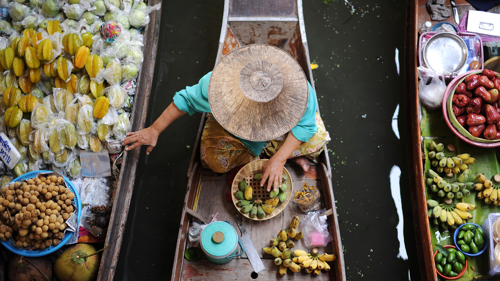 Woman with hat on boat in river
