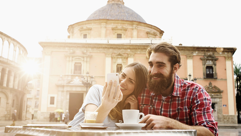 Man and woman having coffee in European city