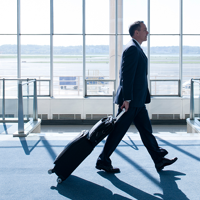 Man walking down airport terminal with suitcase