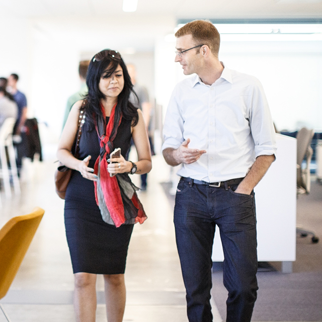 Man and woman walking and talking in office
