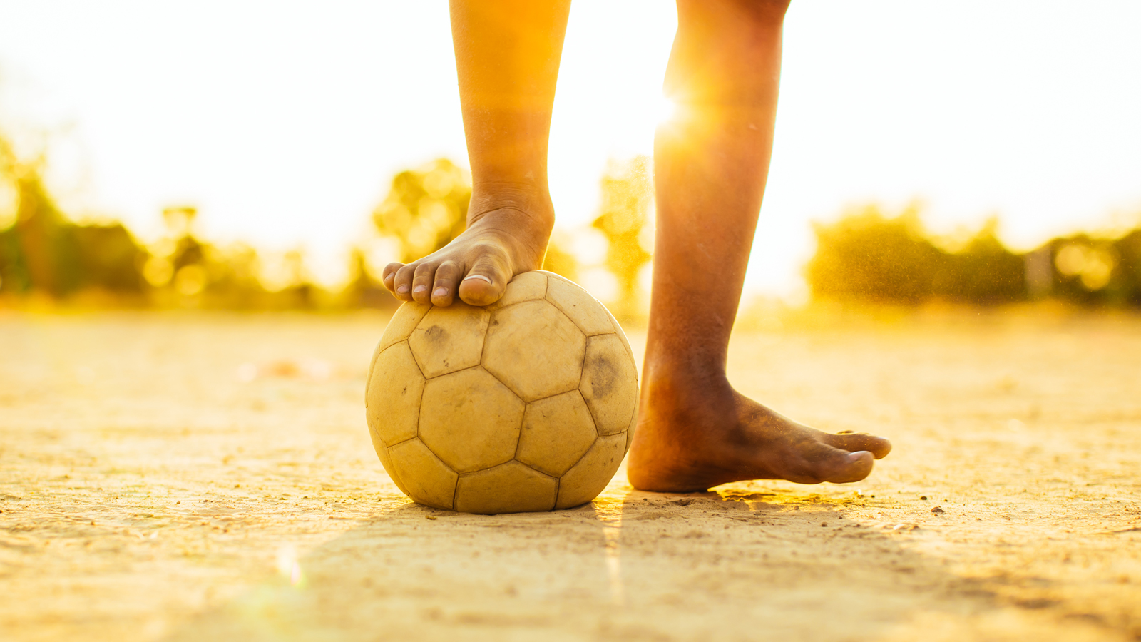 Photo of bare foot on soccer ball