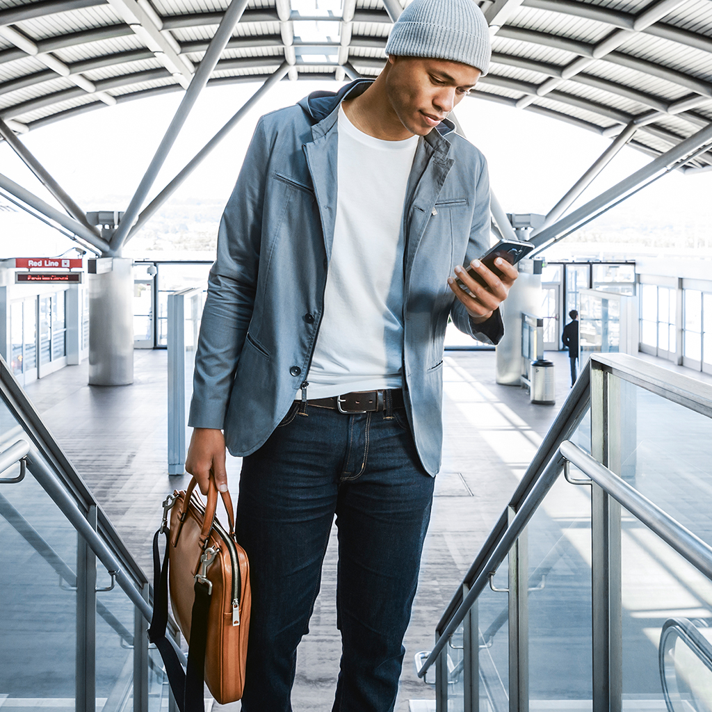 Man looking at smartphone on airport escalator