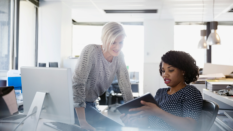 Two women inside an office looking at a tablet.