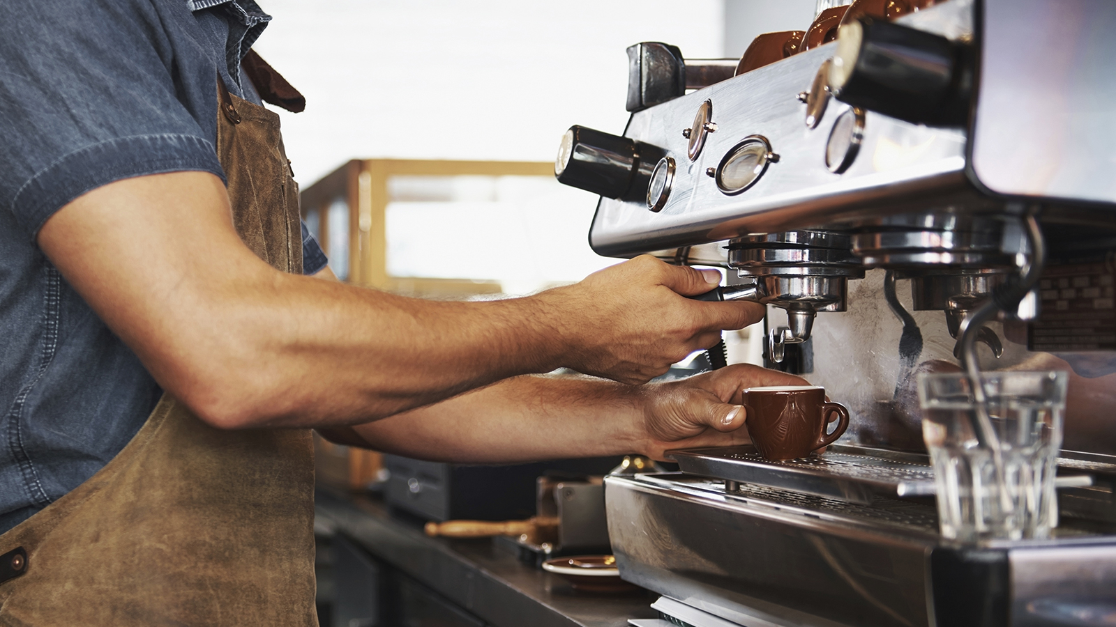 A barista preparing an espresso drink in a coffee shop.