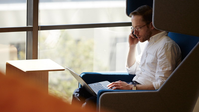 A man sitting in a chair using his mobile phone and laptop.