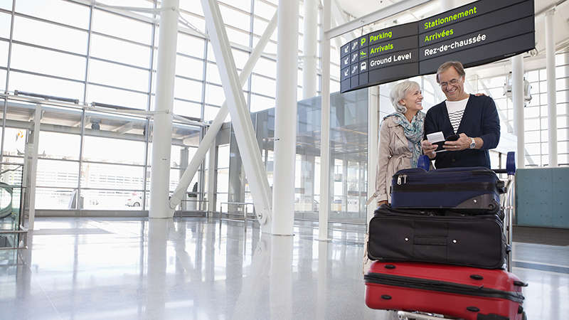 Smiling couple with full luggage trolley in airport.