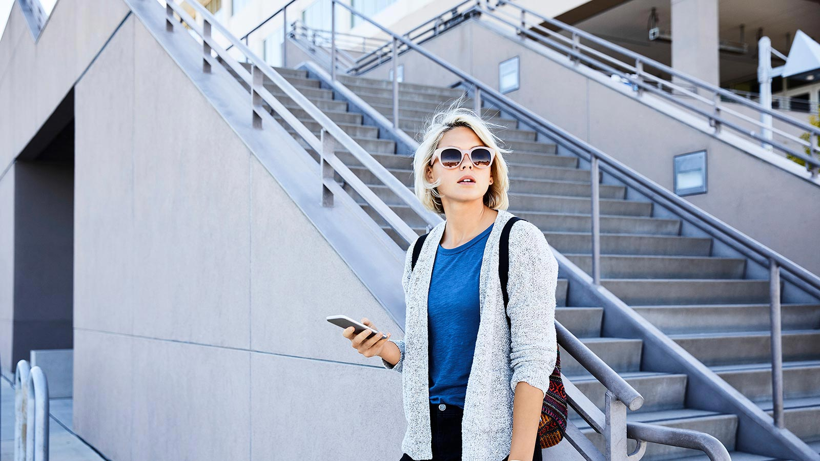 Woman holding a phone and waiting near a stair case.