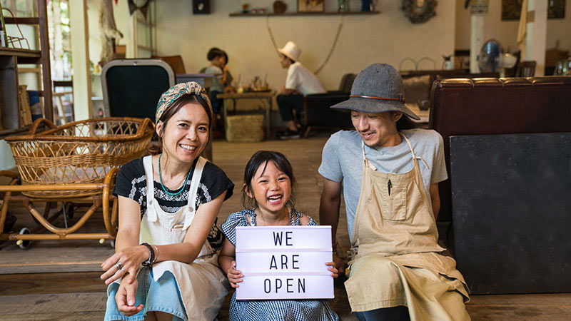 A couple sits outside their shop with their young daughter between them smiling and holding up a sign indicating the store is open.