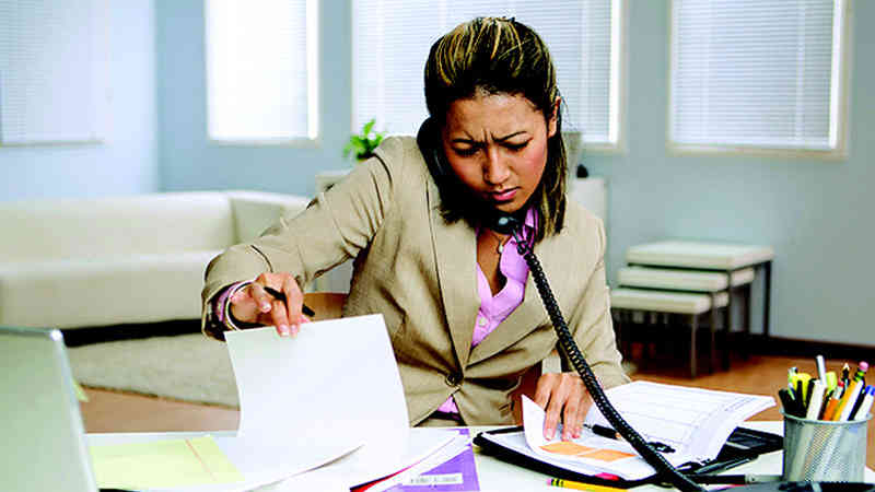A businesswoman is sitting at a desk speaking on the phone with both hands sifting through two separate collection of notes.