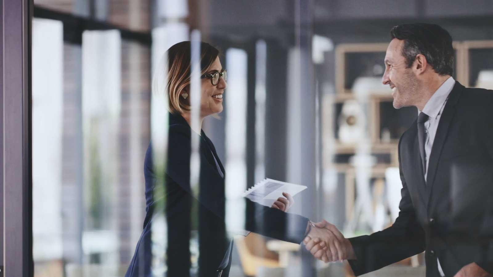 A business woman and business man exchange a handshake in an office.