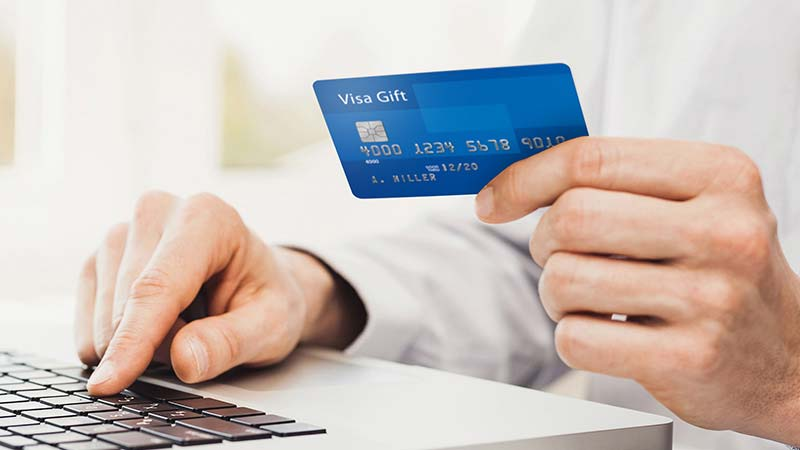 Person using a laptop and holding their Visa Gift Card.