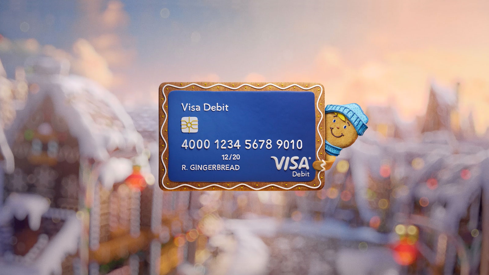 Visa debit card floating in front of a winter scene being held by a gingerbread man.