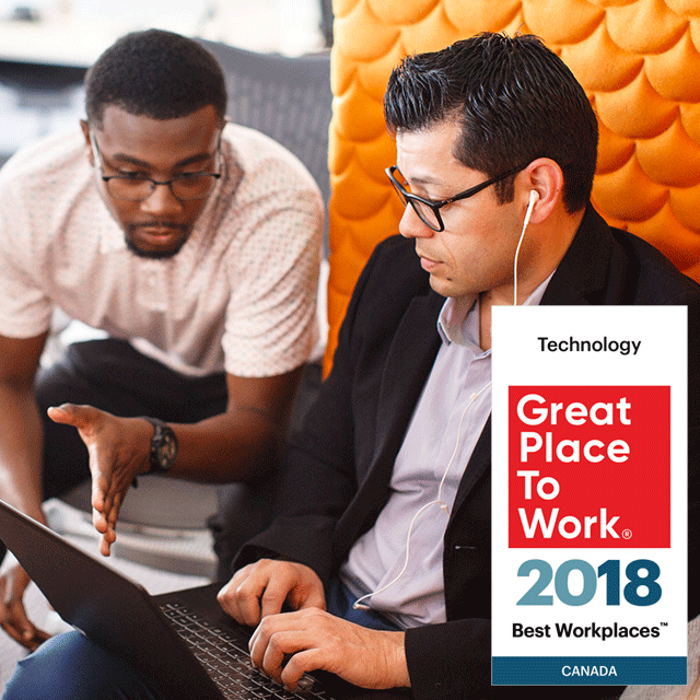 Men talking in office. Visa Canada recognised by Great Place to Work in 2018 as a Best Workplace in Technology.