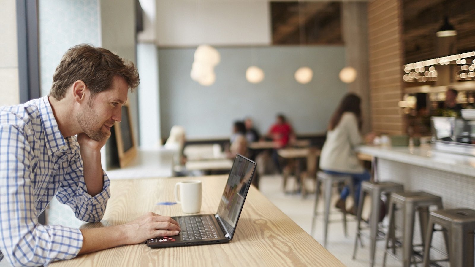 Man viewing his laptop at cafe while having coffee.