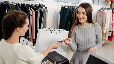 Woman handing credit card to cashier at a clothing store.